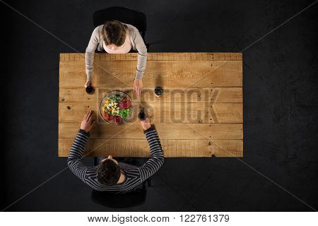 Top view creative photo of couple sitting at wooden vintage table. Man and woman having romantic dinner. They with cheese plate and glasses with wine