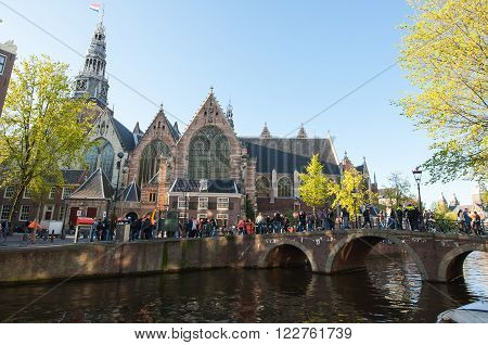 AMSTERDAM-APRIL 27: Old Church as seen from the canal in red light district during King's Day on April 272015. Oude Kerk or Old Church is Amsterdam's oldest building and oldest parish church.