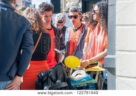 AMSTERDAM-APRIL 27: Unidentified woman sells laughing gas to young men during King's Day on April 27, 2015 in Amsterdam the Netherlands.