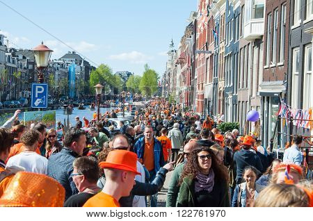 AMSTERDAM-APRIL 27: Locals and tourists celebrate King's Day along bank of Singel canal on April 272015 the Netherlands. King's Day is the largest open-air festivity in Amsterdam.
