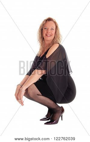 A beautiful blond and happy woman in a black dress crouching on the floor
