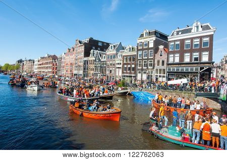 AMSTERDAM-APRIL 27: People in orange on boats participate in celebrating King's Day through Singel canal on April 272015 the Netherlands. King's Day is the largest open-air festivity in Amsterdam.