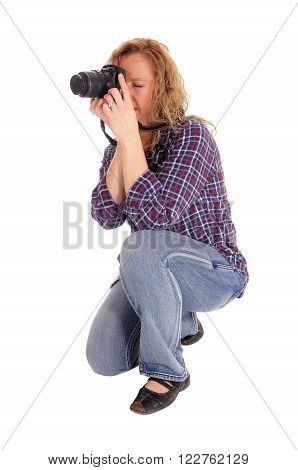 A meddle age women crouching on the floor and taking pictures with a