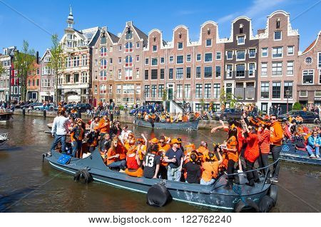 AMSTERDAM-APRIL 27: Locals on the boats participate in celebrating King's Day through Singel canal on April 272015. Kings Day is the biggest open-air festival celebrating the birth of Dutch royalty.