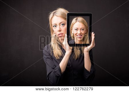 Sad woman showing happy portrait on tablet