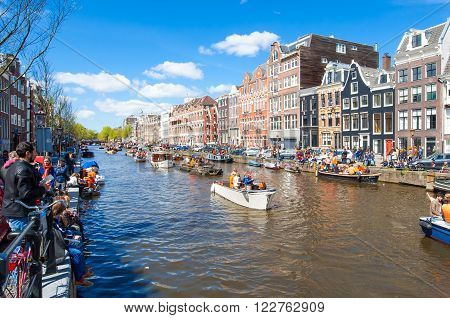 AMSTERDAM-APRIL 27: Locals and tourists celebrate King's Day along the Singel canal on sunny day on April 272015. King's Day is the biggest festival celebrating the birth of Dutch royalty.
