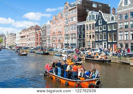 AMSTERDAM-APRIL 27: The celebration of King's Day on a boats along the Singel canal on April 272015 the Netherlands. King's Day is the biggest festival celebrating the birth of Dutch royalty.