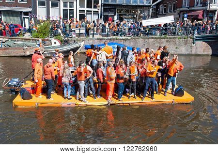 AMSTERDAM-APRIL 27: People in orange celebrate King's Day along the Singel canal on the raft on April 272015. King's Day is the biggest festival celebrating the birth of Dutch royalty.