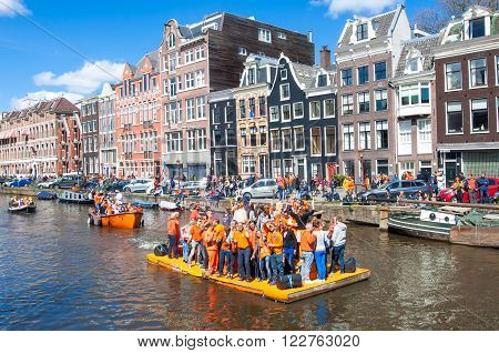 AMSTERDAM-APRIL 27: Happy People celebrate King's Day along the Singel canal on the orange raft crowd enjoy the festival from the bank of the canal on April 272015 the Netherlands.