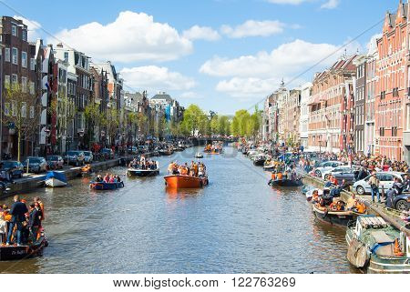 AMSTERDAM-APRIL 27: View of Amsterdam Singel canal full of boats during King's Day on April 272015. King's Day is the biggest festival celebrating the birth of Dutch royalty.