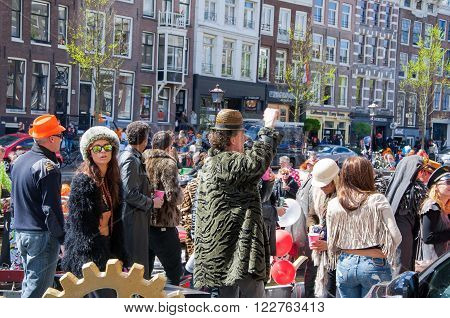 AMSTERDAM-APRIL 27: Unidentified people at the open-air party during King's Day on the Singel canal on April 272015 the Netherlands. King's Day is the largest open-air festivity in Amsterdam.