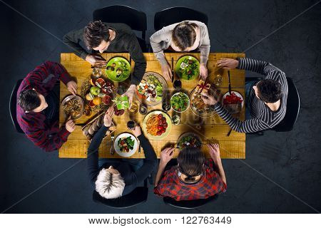 Top view creative photo of friends sitting at wooden vintage table. Friends of six having dinner. They with plates full of delicious meal and glasses with drinks. Man presenting gift to woman