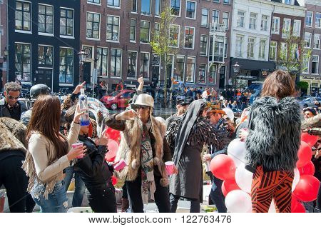 AMSTERDAM-APRIL 27: Unidentified town-dwellers celebrate King's Day on the Singel canal April 272015 in the Netherlands. King's Day is the largest open-air festivity in Amsterdam.