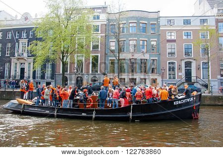 AMSTERDAM-APRIL 27: Locals have dance party on a boat King's Day along the Singel canal on April 272015 the Netherlands. King's Day is the largest open-air festivity in Amsterdam.