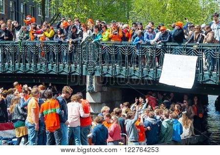 AMSTERDAM, NETHERLANDS-APRIL 27: Boat paty on the Singel canal crowd of people on the bridge on King's Day on April 272015. King's Day is the largest open-air festivity in Amsterdam the Netherlands.