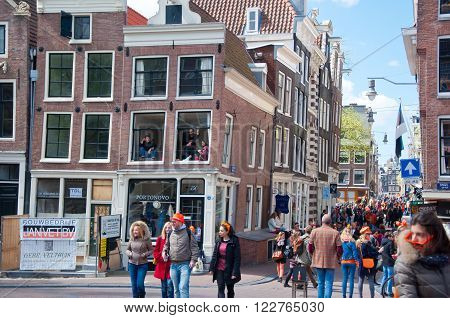 AMSTERDAM - APRIL 27: Crowd of people in orange celebrate King's Day around Amsterdam street on April 27, 2015. King's Day (Koningsdag) is held on 27 April (the king's birthday) every year.