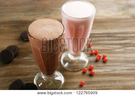 Glasses of chocolate and fruit milkshakes with berries and cookies on wooden background