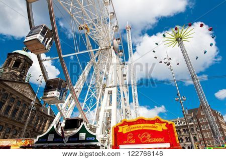 AMSTERDAM, NETHERLANDS-APRIL 27: Ferris wheel on Dam Square during King's Day on April 272015 in Amsterdam. King's Day is the largest open-air festivity in Amsterdam.