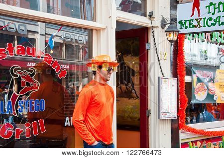 AMSTERDAMNETHERLANDS-APRIL 27: Local in traditional orange on King's Day on April 2727 in Amsterdam. King's Day is the largest open-air festivity in Amsterdam.