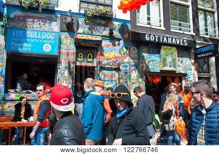 AMSTERDAMNETHERLANDS-APRIL 27: Tourists go by Amsterdam coffeeshop in red-light district on King's Day on April 272015 the Netherlands. King's Day is the largest open-air festivity in Amsterdam.