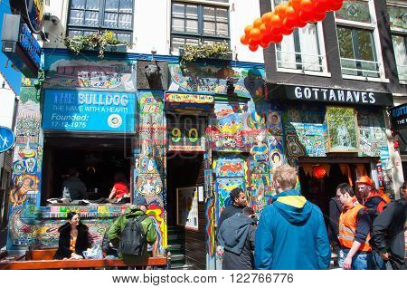AMSTERDAM NETHERLANDS APRIL 27: Famous Amsterdam Bulldog coffeeshop in red-light district in the midday on King's Day on April 272015. King's Day is the largest open-air festivity in Amsterdam.