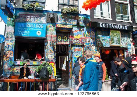 AMSTERDAMNETHERLANDS-APRIL 27: Tourists go by Bulldog coffeeshop in red-light district on King's Day on April 272015 the Netherlands. King's Day is the largest open-air festivity in Amsterdam.