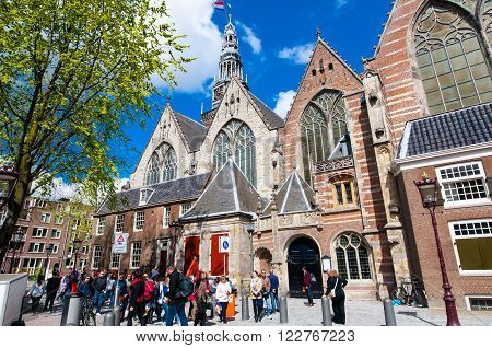 Amsterdam-April 27: Oude Kerk in De Wallen group of tourists go sightseeing on April 272015 in Amsterdam the Netherlands. The Oude Kerk is Amsterdam's oldest parish church consecrated in 1306.