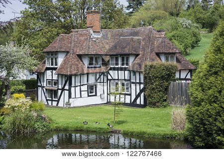LOOSE KENT UK 11 MAY 2015 - Pretty half timbered cottage in the village of Loose Kent UK with the Loose river in the foreground