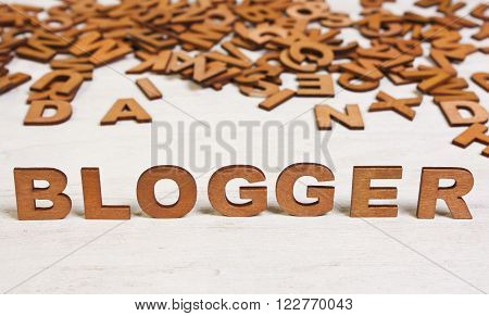 blogger word of wooden letters on a white background old wooden