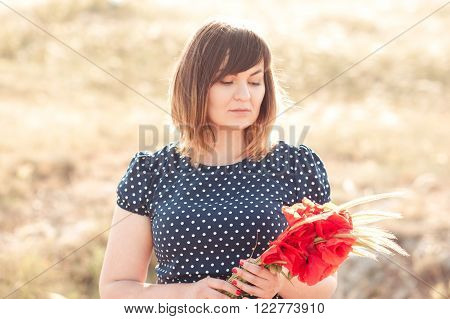 Blonde girl 20-24 year old holding poppies closeup outdoors. Young adults. Summer time.