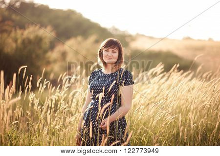 Beautiful girl 25-27 year old walking at meadow. Summer time. Wearing trendy dress with polka dots. Young adult.