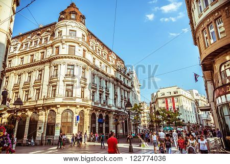 BELGRADE SERBIA - SEPTEMBER 23: People walking on Knez Mihajlova most famous shopping thoroughfare and one of the favorite tourist destinations in Belgrade on September 23 2015 in Belgrade Serbia. Filtered photo with warm summer lighting.