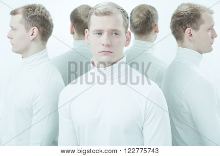 Sick young man with split personality standing in white interior poster