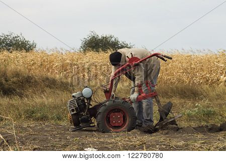 DIKANKA UKRAINE - SEPTEMBER 30 2015: Country farmer is plowing his garden with walk-behind garden tractor against the backdrop of a corn field