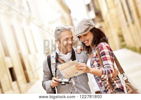 Cheerful couple looking at map, week-end tour