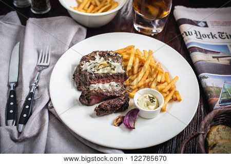 Healthy lean grilled medium-rare steak with french fries, and  whiskey glass and a spice in a rustic pub or tavern. Food-styling