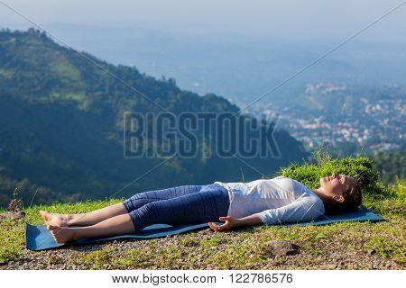 Woman relaxes in yoga asana Savasana - corpse pose outdoors in Himalayas. Himachal Pradesh, India