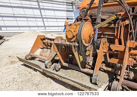 Plate compactor is mounted to the truck compacting sand at road construction site.