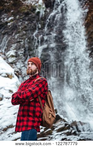 Thoughtful man with backpack and arms folded standing near a waterfall outdoors and looking away