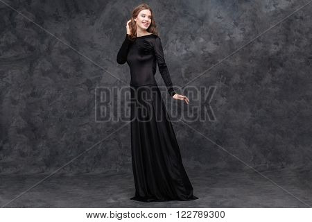 Full length portrait of charming young woman in long black dress standing and looking away over grey background