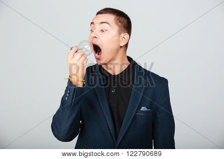 Man trying to eat bulb isolated on a white background