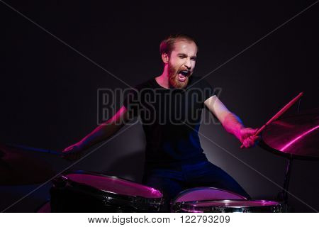 Handsome male musician playing the drums