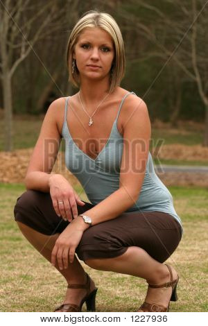 Young Model Squatting In Brown Capris