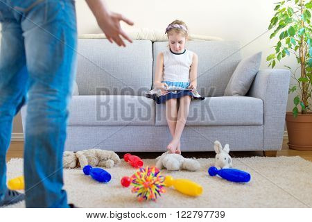It's time to clean up your toys! Little girl playing with tablet pc ignoring her father.