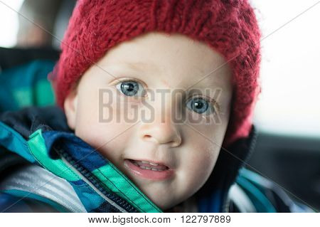 Portrait of a 3 year old boy in winter looking at the camera