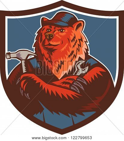 Illustration of a builder handyman Russian bear or Eurasian brown bear wearing hat arms folded with tools hammer and wrench facing front set inside crest shield done in retro woodcut style.