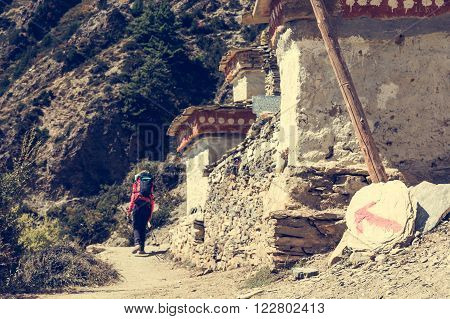 Female trekker following a direction sign. Annapurna circuit in Nepal.