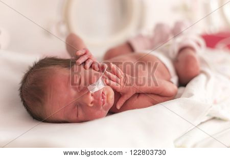Premature newborn baby girl in the hospital incubator after c-section in 33 week