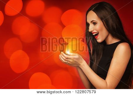 Surprised beautiful woman holding jewelry box with an engagement ring in it. Happy young woman after marriage proposal. Red background.