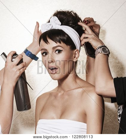 Backstage photo bridal rituals before wedding. Beautiful brunette woman with retro hairdo and makeup. Luxury vogue style model posing in studio. Bridal makeup and wedding ideas concept.
